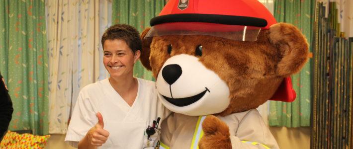 Brannbamsen Bjørnis besøker barneavdelingen på sjukehuset i Elverum